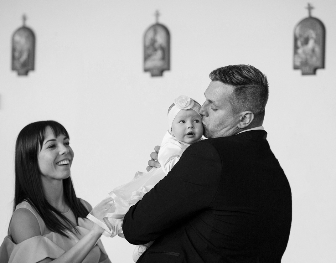 Man holding baby with woman looking and smiling at baby