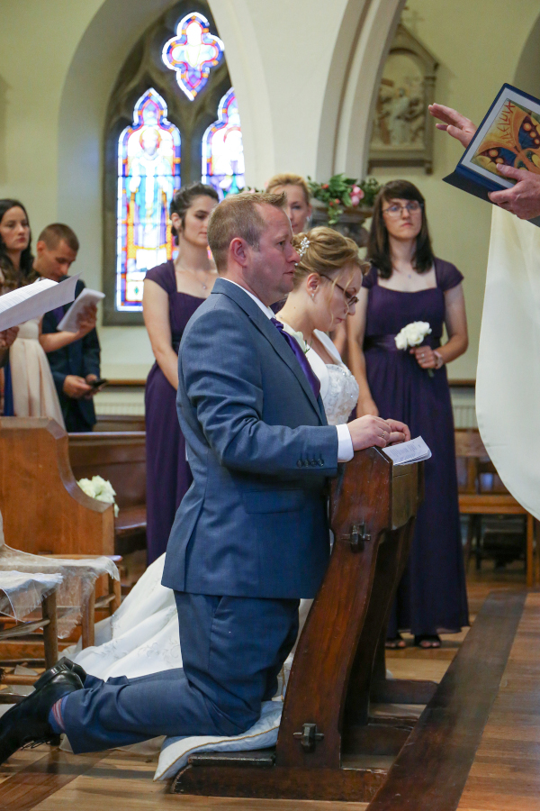 Man and woman kneeling at a wedding ceremony