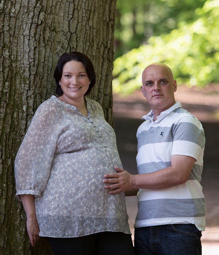 Pregnant woman and man standing in front of a tree