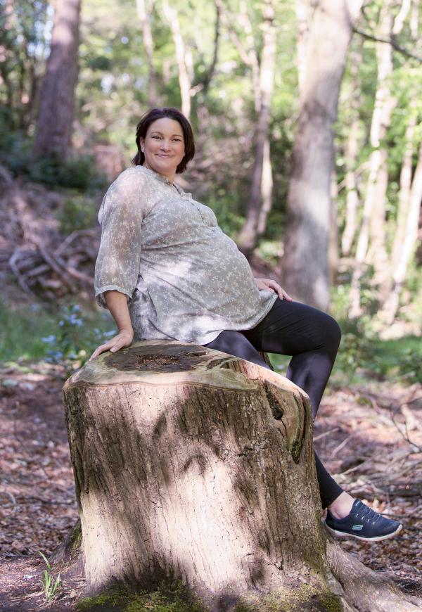 Pregnant woman sitting on a tree stump